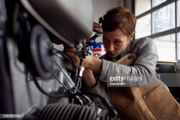 woman working in repair workshop - handgemacht stock-fotos und bilder