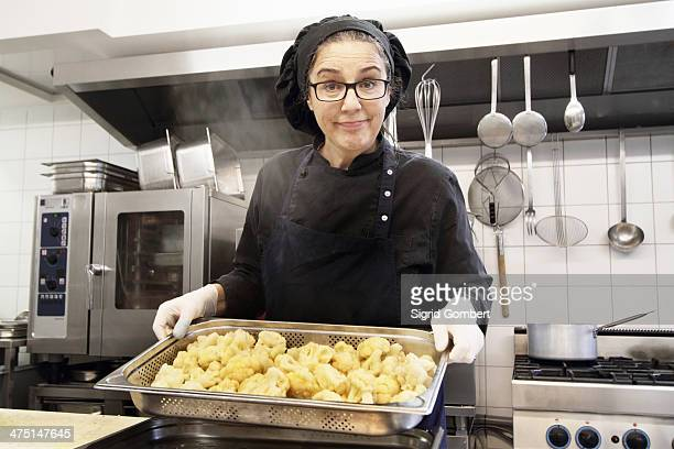 woman working in restaurant kitchen, holding tray of cauliflower - sigrid gombert stock-fotos und bilder