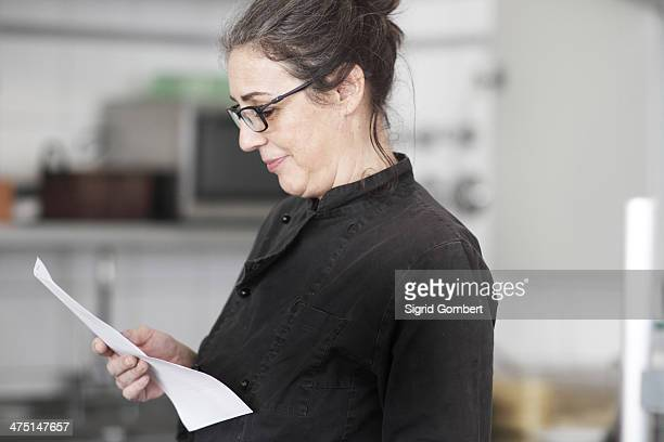 woman working in restaurant kitchen, reading order - sigrid gombert stock-fotos und bilder