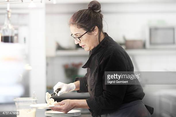 woman working in restaurant kitchen, serving meal - sigrid gombert stock-fotos und bilder