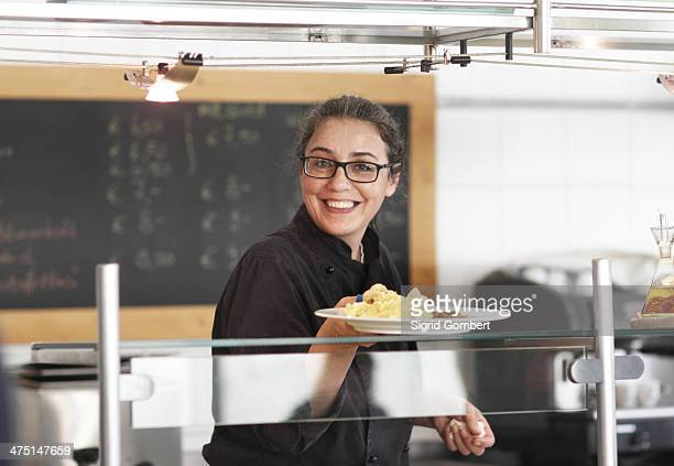 woman working in restaurant kitchen, serving meal - sigrid gombert fotografías e imágenes de stock
