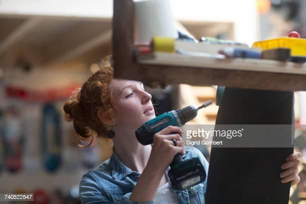 Woman working in skateboard shop, attaching wheels to skateboard