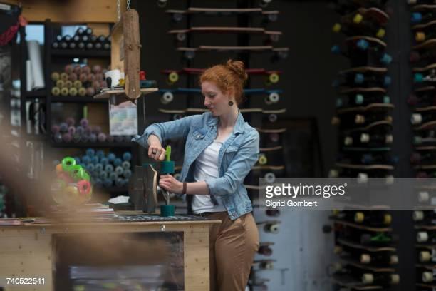 woman working in skateboard shop, checking wheels on skateboard - sigrid gombert stock-fotos und bilder