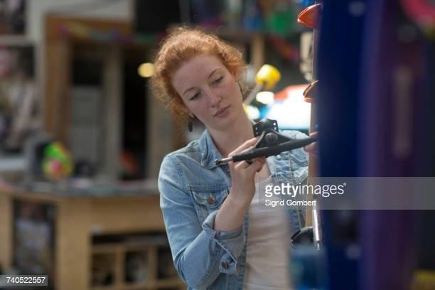 woman working in skateboard shop, inspecting skateboard trucks - sigrid gombert stock-fotos und bilder