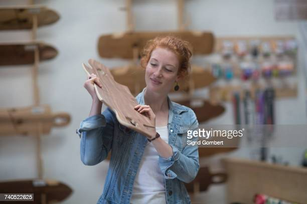 woman working in skateboard shop, inspecting wooden board - sigrid gombert stock-fotos und bilder
