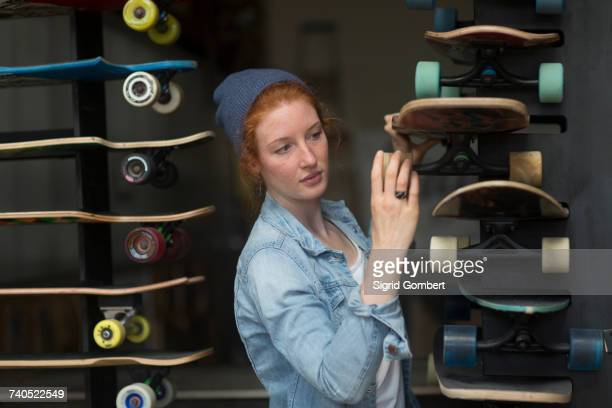 woman working in skateboard shop, organising skateboard display - sigrid gombert stock-fotos und bilder