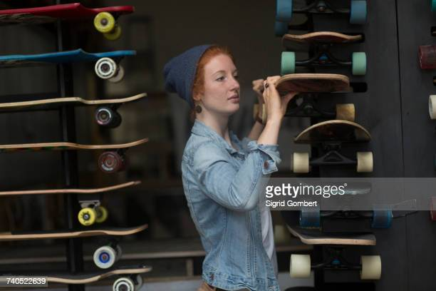 Woman working in skateboard shop, organising skateboard display