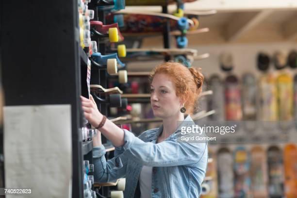 woman working in skateboard shop, putting skateboard on shelf - sigrid gombert stock-fotos und bilder