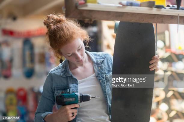 woman working in skateboard shop, using hand tool to remove skateboard wheel - sigrid gombert stock-fotos und bilder