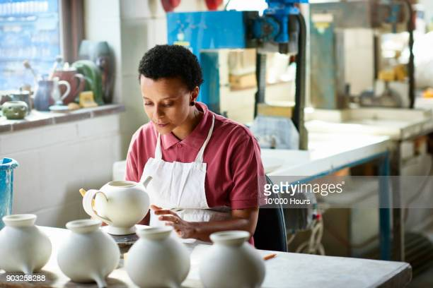 Woman working in small pottery factory