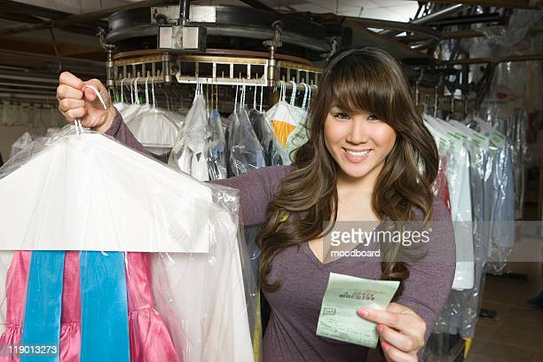 woman working in the laundrette holding a receipt and clothes - dry cleaner stock pictures, royalty-free photos & images