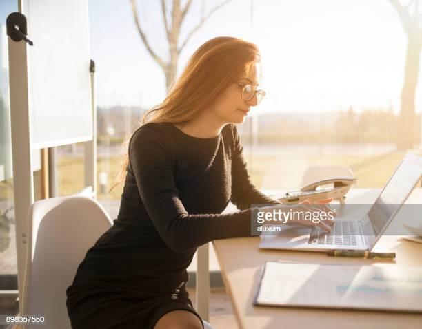 Mujer que trabaja en la oficina con su computadora portátil