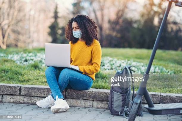 woman working in the park during coronavirus social isolation - student stock pictures, royalty-free photos & images