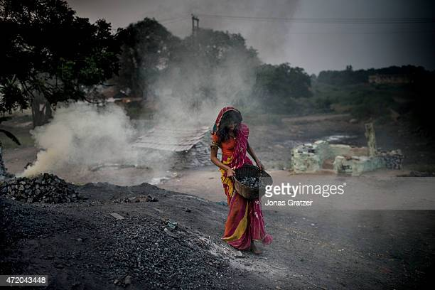 A woman working in the toxic smoke that comes out of the ground methane and other toxic gases constantly spew out from the open wounds in the Earth's...
