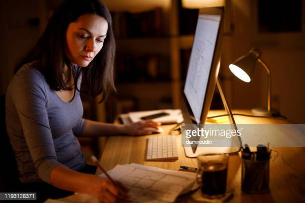 woman working late at home - damircudic stock photos and pictures