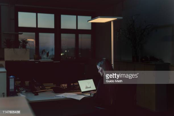 woman working late in office. - urgency stock pictures, royalty-free photos & images