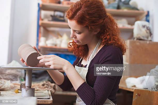 Donna lavorando su un vaso di argilla