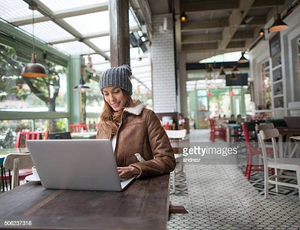 Woman working on a laptop at a restaurant