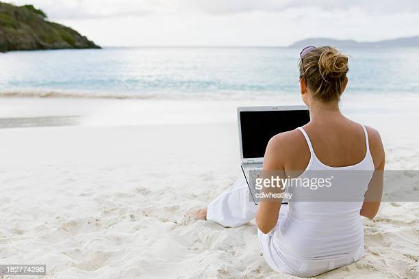 woman working on a laptop at Caribbean beach
