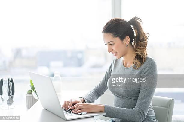 Mujer trabajando en un ordenador portátil en su hogar