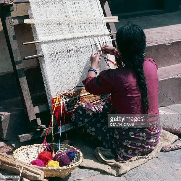 Woman working on a loom weaving a rug Pokhara Nepal