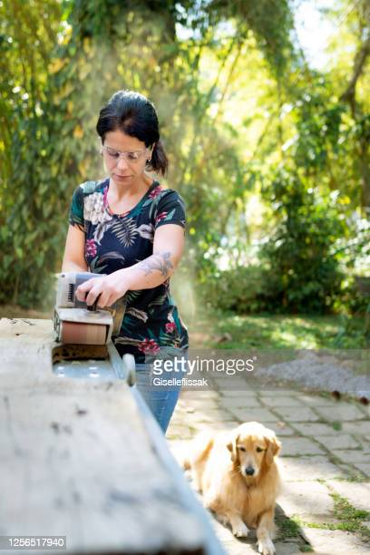 woman working on a peace of wood, making home improvements - personal accessory stock pictures, royalty-free photos & images