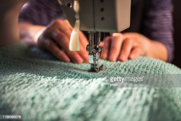 woman working on a sewing machine - fashion industry stock pictures, royalty-free photos & images