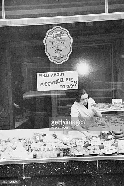 A woman working on a tripe stall in Wigan Lancashire November 1939 A sign asks 'What about a cowheel pie today' Original publication Picture Post 228...