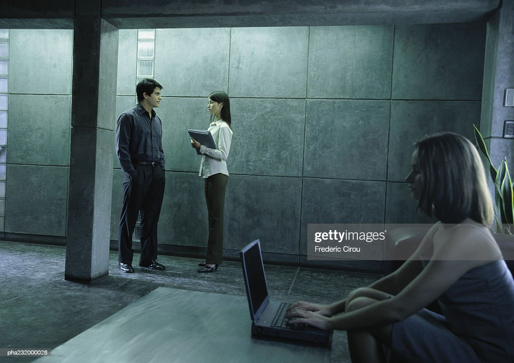 Woman working on computer, man and woman talking nearby. : Stockfoto