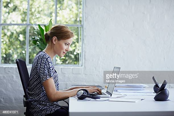 woman working on computer - concentratie stockfoto's en -beelden