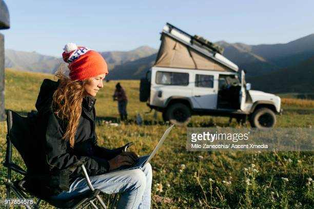 woman working on computer while 4x4 camping in mountain meadow - red jacket stock pictures, royalty-free photos & images