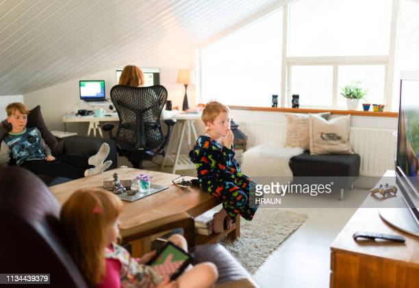 woman working on computer while children relaxing - working from home stock pictures, royalty-free photos & images