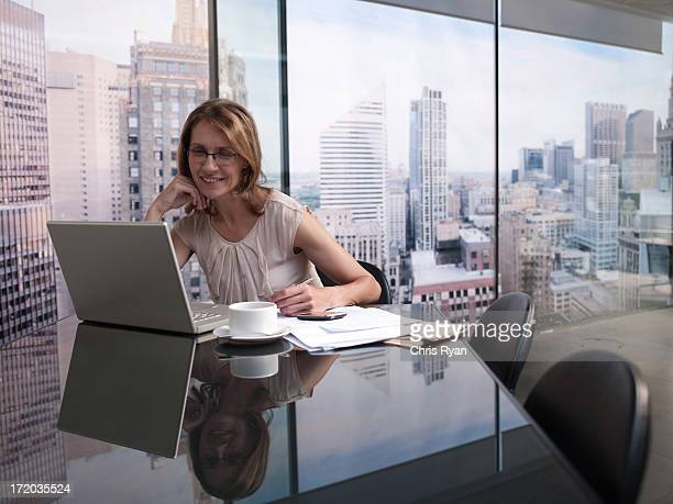 Woman working on computer with cityscape in background