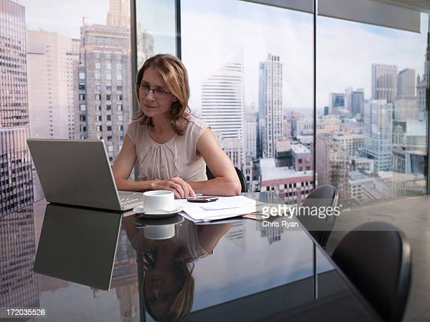 Femme travaillant sur ordinateur dans la ville en toile de fond