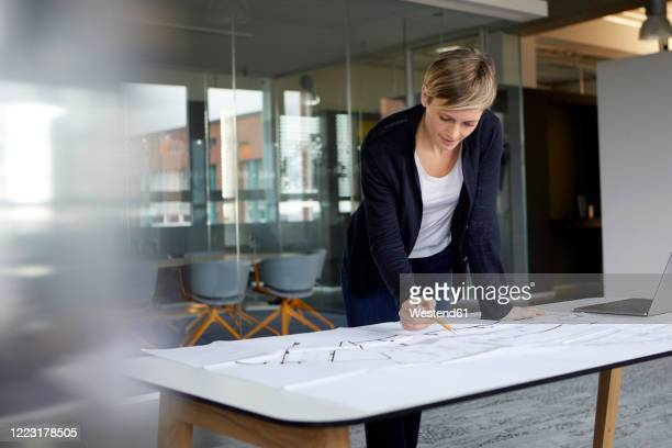 woman working on construction plan in office - 女性建築家 ストックフォトと画像