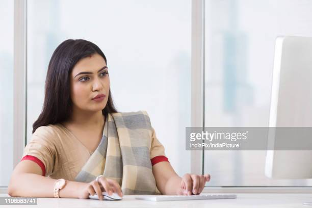 woman working on desktop - sari stock pictures, royalty-free photos & images