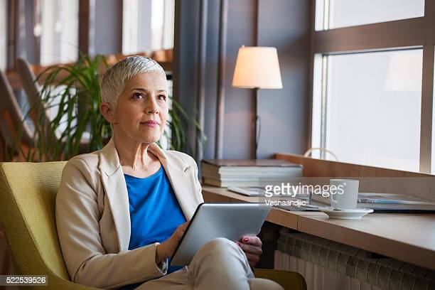 Woman working on digital tablet at cafe