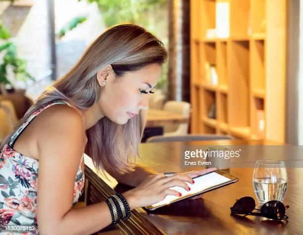 Woman working on digital tablet in coffee shop