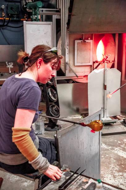 Woman working on Glassblowing figures in her workshop