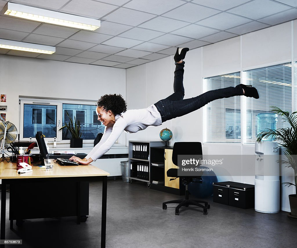 Woman working on her computer floating above the f : Photo