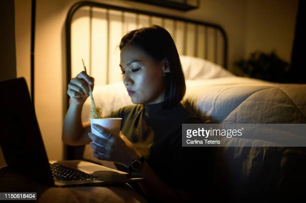 woman working on her laptop in her bedroom at night - noodles stock pictures, royalty-free photos & images