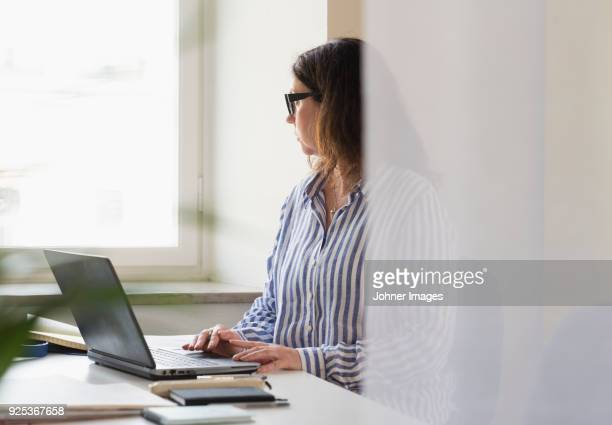 Woman working on laptop and looking through window in office
