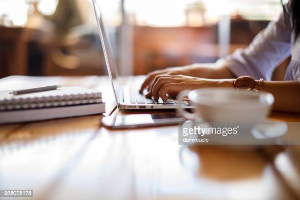 woman working on laptop at a cafe - online class stock pictures, royalty-free photos & images