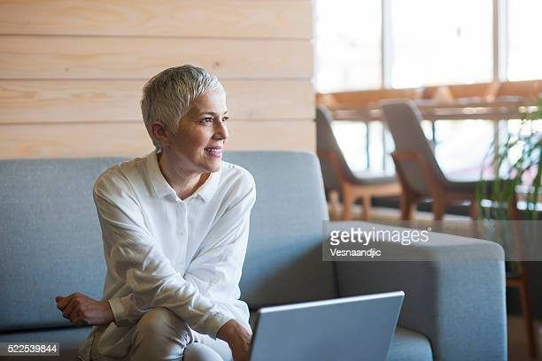 Woman working on laptop at cafe