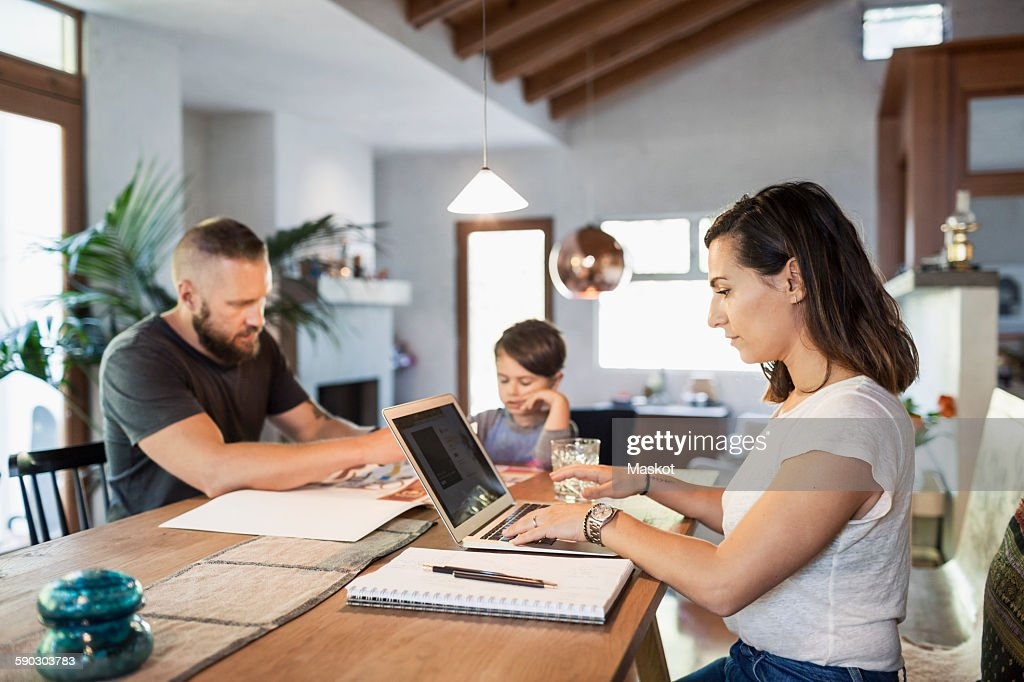 Woman working on laptop at dining table with family in background : Stock Photo