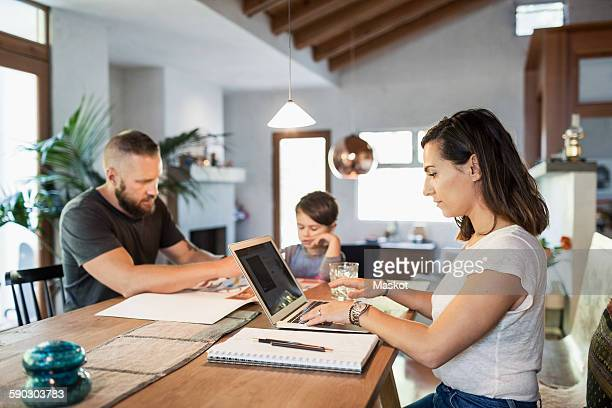 Woman working on laptop at dining table with family in background