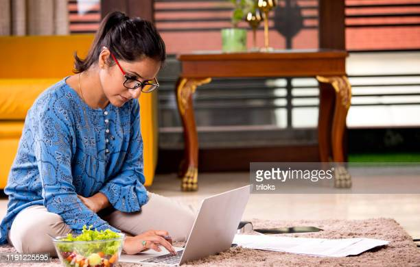 woman working on laptop at home - indian ethnicity stock pictures, royalty-free photos & images