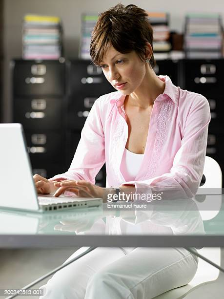 woman working on laptop computer - fully unbuttoned stock pictures, royalty-free photos & images