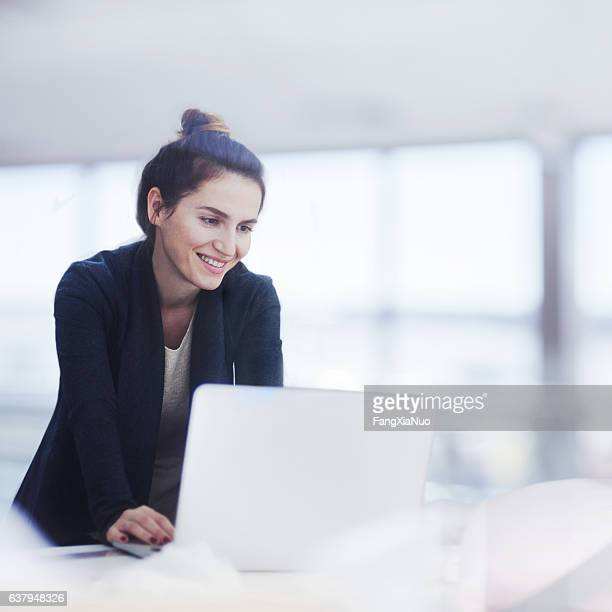 woman working on laptop in bright office - brightly lit stock pictures, royalty-free photos & images