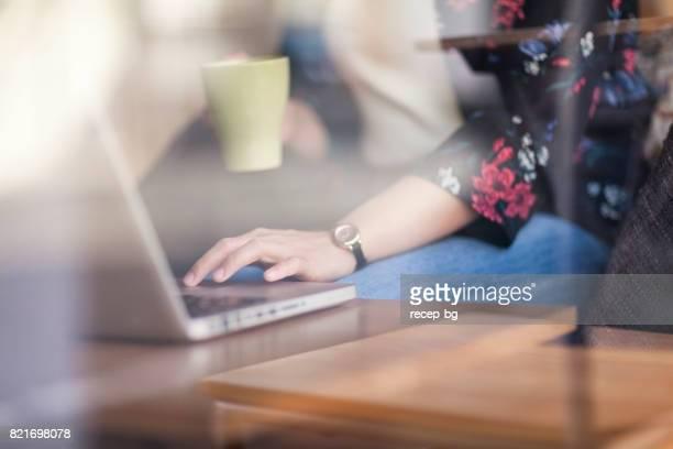 カフェでのラップトップの働く女性